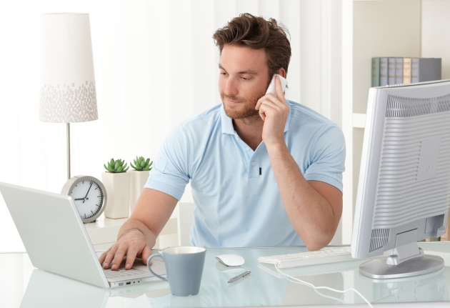 Casual businessman working at office desk, using mobile phone an